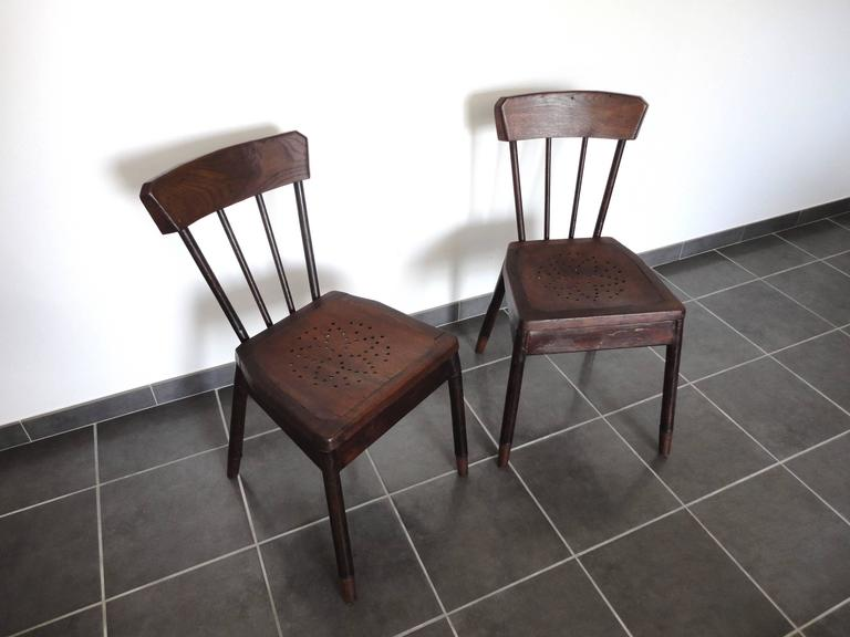 Pair of chairs attributed to Albert Armand Rateau. Made in France in the late 1920s.  The structure is made from metal with a faux wood paint, the backrest and the seat are made from solid oak. They were part of the decoration of the Sick Children's