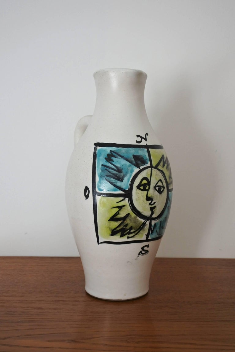 Pitcher vase by renowned french pottery artist Georges Jouve. Glazed earthenware. Hand painted decor on the vase showing the 4 cardinal points with a sun in the middle. Signed with the artist's cypher.  Circa 1955 Decor documented in the book