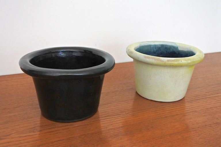 Pair of ceramics by renowned french potter Goerges Jouve. One pot shows a black metallic glaze, the other pot a white crackled glaze with light yellow accents. Both pieces are signed with the artist's mark and a fine example of his exceptional