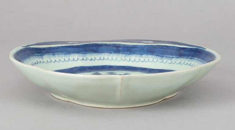 Chinese Export Canton blue and white porcelain lobed shrimp dish, the flange decorated with two eyes, the centre decorated with pagodas, a bridge, boats, trees and rockery.