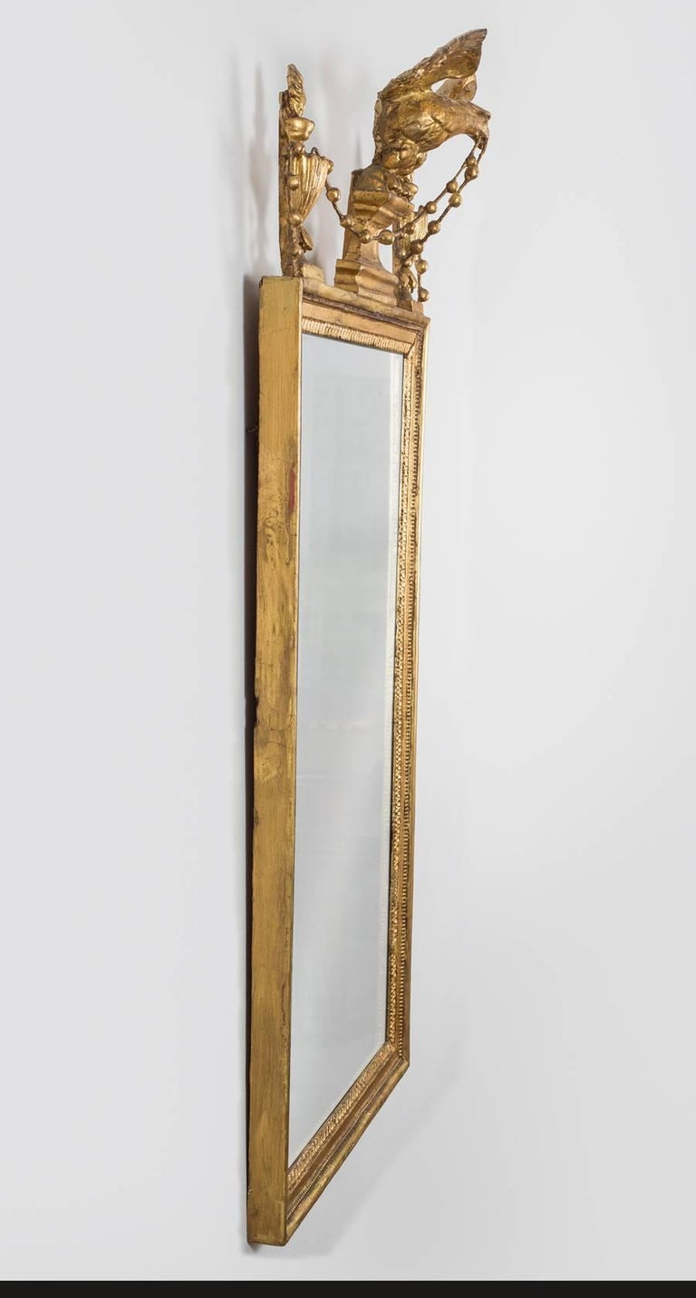 Sheraton period neoclassical giltwood pier mirror, the rectangular mirror plate within a molded and beaded frame edged with egg and dart design, surmounted and centered by a winged eagle perched on a shaped plinth, flanked by flaming urns and joined