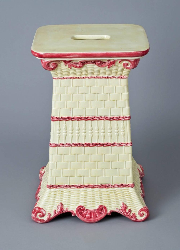 Antique Wedgwood garden seat decorated with four different basket weave designs each separated by dark pink chains, the top with open handle, the top edge outlined in pink, the top and shaped base of shells also decorated in dark pink. The inside