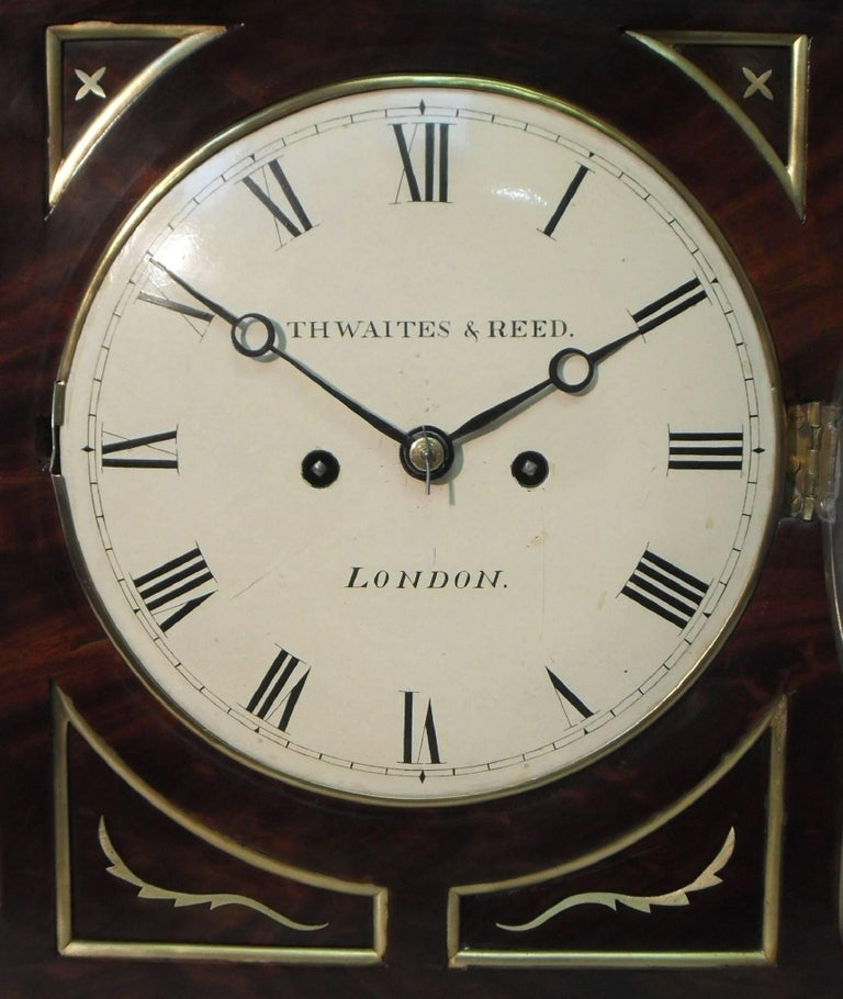 An extremely good quality English figured mahogany chamfer top bracket or table clock with ebony moulding, decorative brass inlay, inset corner panels and brass moulded edges to the front stood on brass ball feet finished with a pineapple finial to