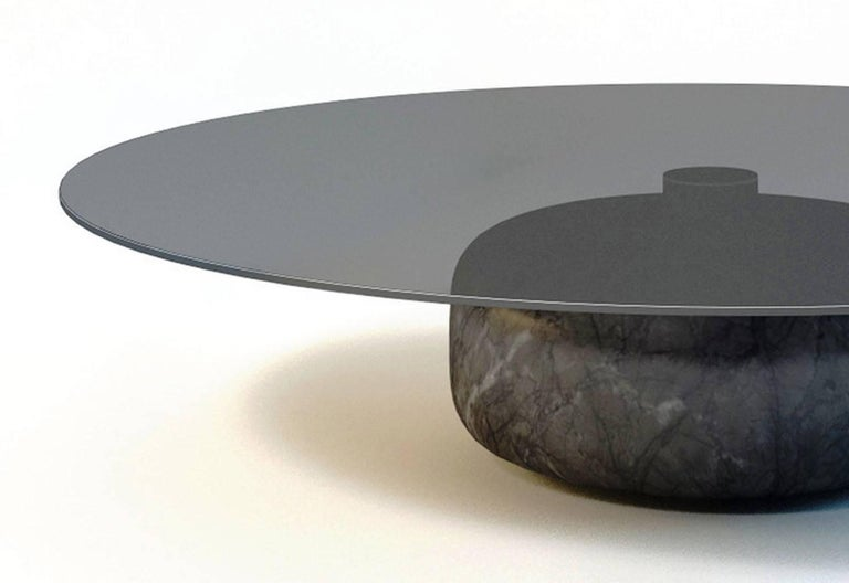 Marble and Glass unite for the Inoa coffee table designed by Christophe Pillet. A distinct, rounded marble base balances a defiant polished glass top creating a contemporary piece with simple, strong lines and a luxurious feel.   The handcrafted,
