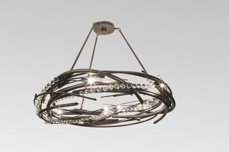 The circular motion of this highly sculptured chandelier represents the movement of an object along a circular path. The non-uniform changing rate of rotation describes the shape of the chandelier with its crystal bundles attached by the result of