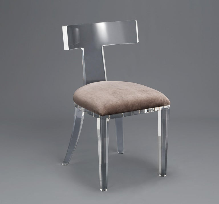 A set of four dining chairs crafted from one solid piece of Lucite and upholstered in taupe grey velvet. These dining chairs offer a combination of strength, comfort, and style to create a timeless design while heavy duty construction allows for