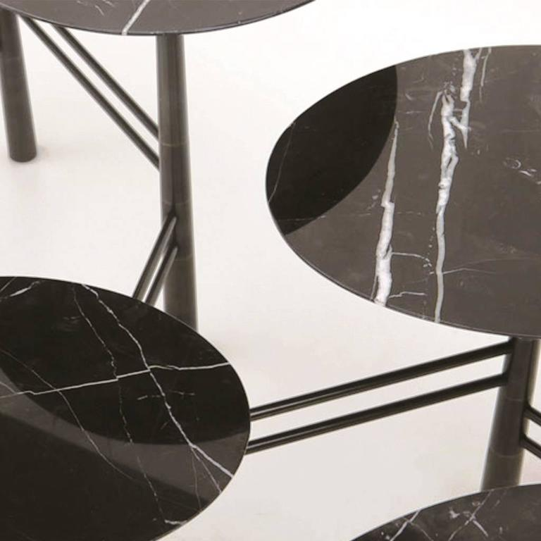 Inspired by pebbles on the beach, this contemporary coffee table is expandable and contractible with seven marble tops in Nero marquina and black lacquer steel base. The base is a masterpiece of sophisticated engineering. Solid steel uprights are