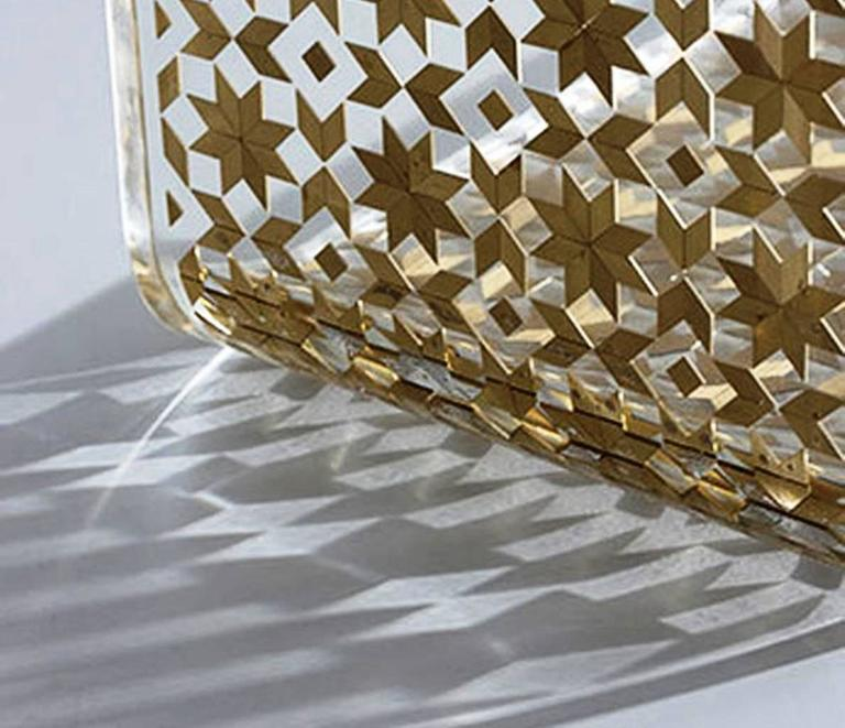 The C Resin side table by Nada Debs is composed of transparent resin with hand inlay of mother-of-pearl, brushed silver metal or brushed brass and copper metal; reflecting the beauty of Arabesque geometric designs.   This practical table slides