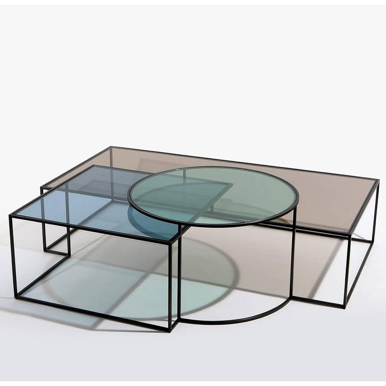 The Geometrik coffee table by the architect Nada Debs is a composition of three geometric shapes. Shadows are created through the overlapping of forms. Blackened steel frame glass: Colored in three soft shades of red, blue and green.  Dimensions: