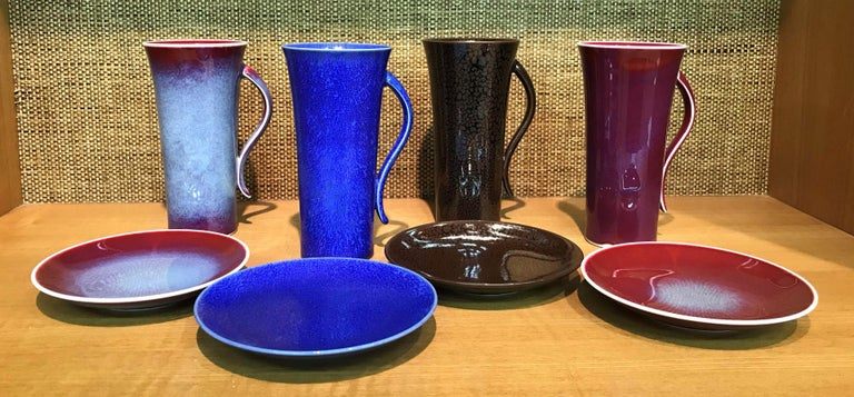 Extraordinary set of four contemporary Japanese tall hand glazed porcelain mugs/cups and matching dessert plates, handsomely proportioned and masterfully glazed in the artist's signature blue, wine-red and chocolate brown, signed pieces by widely