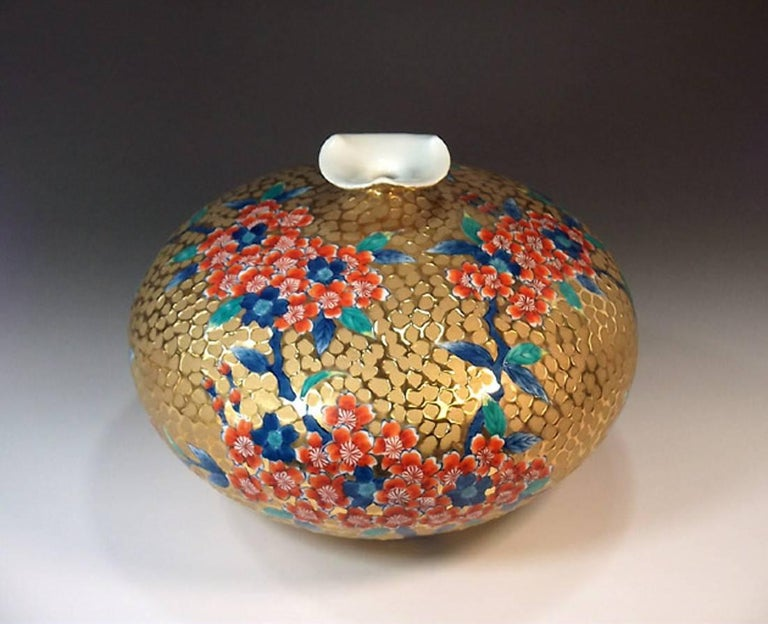 This exquisite rotund shape gilded and dimpled porcelain vase decorated with cherry blossoms in iron red is by Kinsai, a widely respected master porcelain artist in Imari-Arita style.