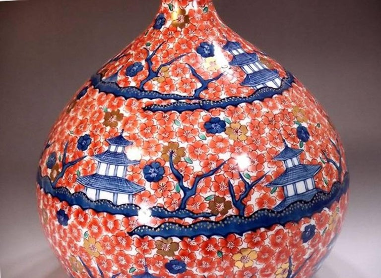 This exquisite very large Japanese contemporary porcelain vase hand-painted on an elegant gourd shape body, depicting plum blossom in red and medieval palaces in shades of blue, is a signed work of Tadashi, highly acclaimed Japanese master porcelain