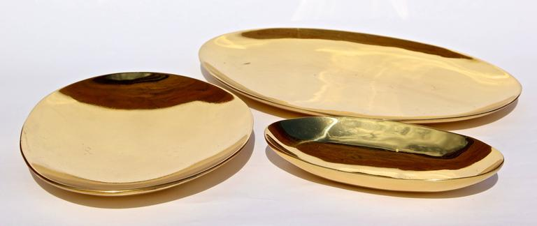 Set of three handmade cast brass plates with a polished finish.   Very charming as a decorative object, they work very well and plates for pillar candles.  Measures: Large 240 x 165 x 15 mm Medium 190 x 145 x 23 mm Small 150 x 85 x 23 mm.