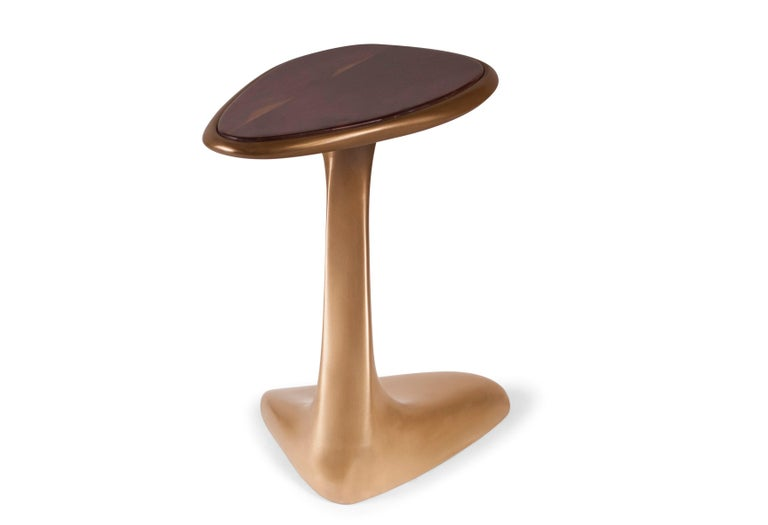 The palm side table is made out of wood with our custom gold finish with high polished walnut top.