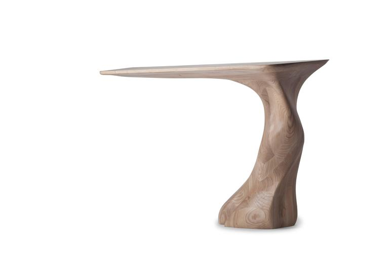 Frolic console table is a stylish futuristic sculptural art table with a dynamic form designed and manufactured by Amorph. Frolic console table is made out of solid ash wood natural stain with natural stained finish. By the nature, the ash wood