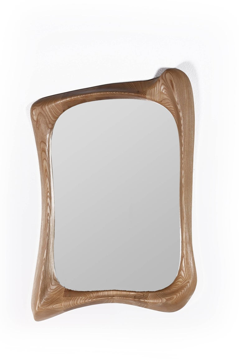 Narcissus mirror is a stylish futuristic sculptural art mirror frame with a dynamic form. Narcissus is made out of solid ashwood with natural stained finish. By the nature, the ashwood grain's look would be slightly different from the other.