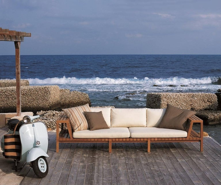 Roda Network 130 outdoor teak sofa made in solid teak wood and grey polyester belts. The brilliant providence of the project has been to turn the teak skeleton into a perfect shelf to hold the accessories of rest and relaxation. The structure offers