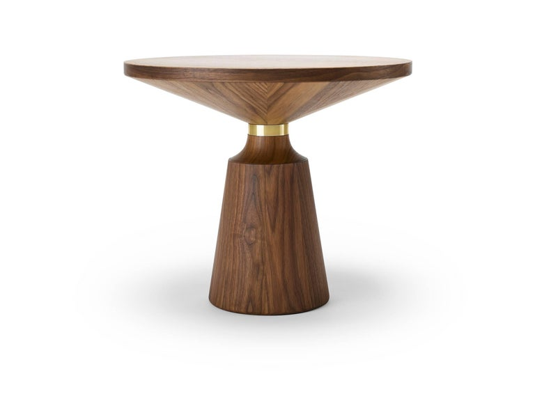 Turned by hand and using both solid and veneered timber, the Nicole Occasional table has a simple but graphically striking Silhouette punctuated by the metal collar. The Nicole occasional table is shown here in natural oiled walnut and brass, and