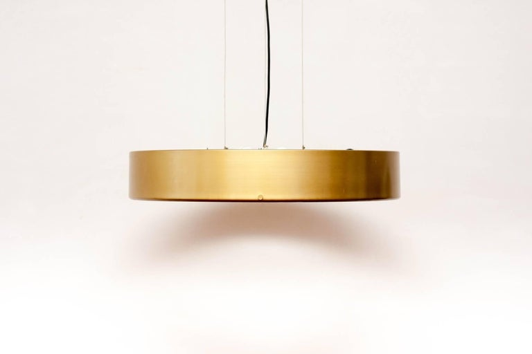 Large pendant light designed by Stilnovo founder Bruno Gatta, 1959. Rare original golden color. The lamp is suspended from a ceiling plate by three metal wires each which can be adjusted to change height and each pendant lamp holds six armatures. I