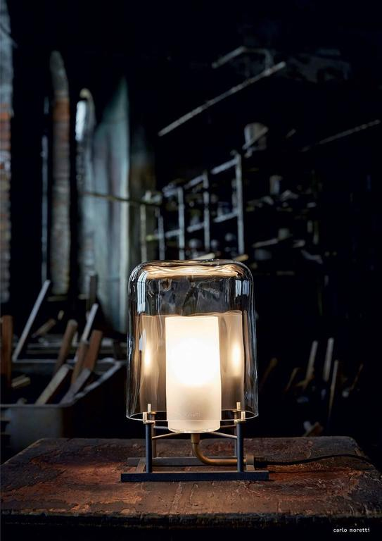 Table lamp of clear mouth blown Murano glass, anthracite painted iron and natural brass designed in 1984 by Carlo Moretti and Paolo Martinuzzi. 