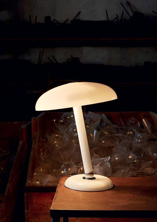 An adjustable table lamp in milk white Murano glass designed in 1978 by Carlo Moretti.   Two x 60 watt incandescent bulbs, two x 42 watt ecolamp E27 socket.   Carlo Moretti: An artisan factory  Strolling afoot through the foundations of