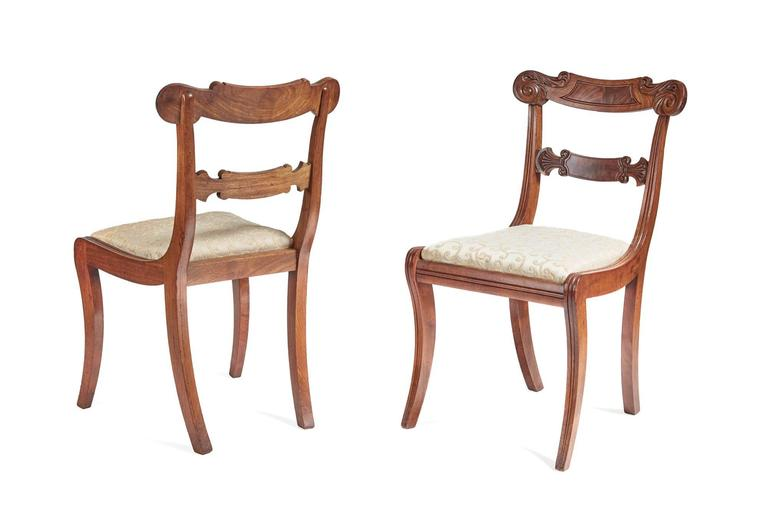 A fine set of six Regency mahogany dining chairs, consists of five singles and oene carver, shaped top rail reeded panel and carved decoration, carved central, the carver chair has a lovely scrolled reeded arm, supported by elegant reeded sabre