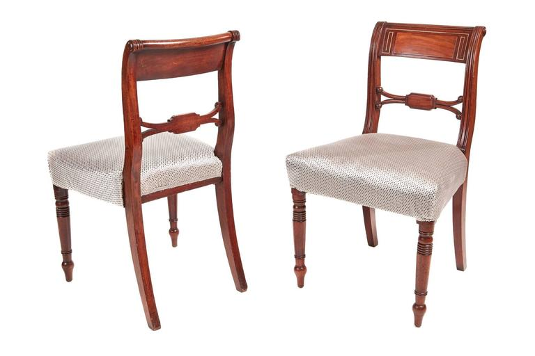 Set of six Regency mahogany brass inlaid dining chairs, with a shaped reeded and brass inlaid top rail, shaped centre splat, standing on turned legs to the front outswept back legs