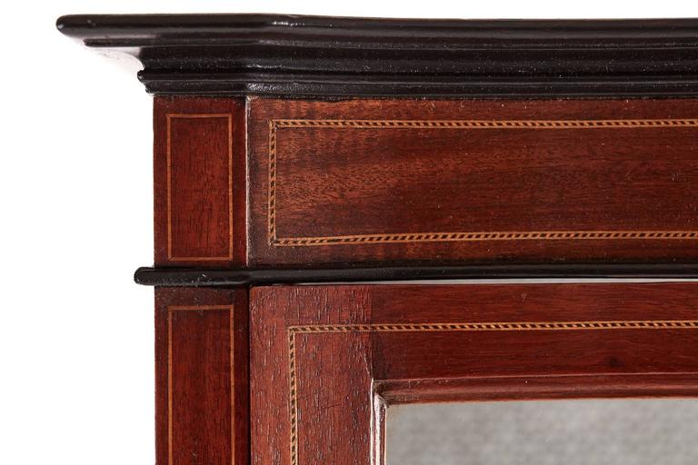 Edwardian inlaid mahogany serpentine front display cabinet, with a inlaid top frieze, serpentine shaped glazed door, two glass display shelves interior, raised on square inlaid tapered legs Lovely color and condition.