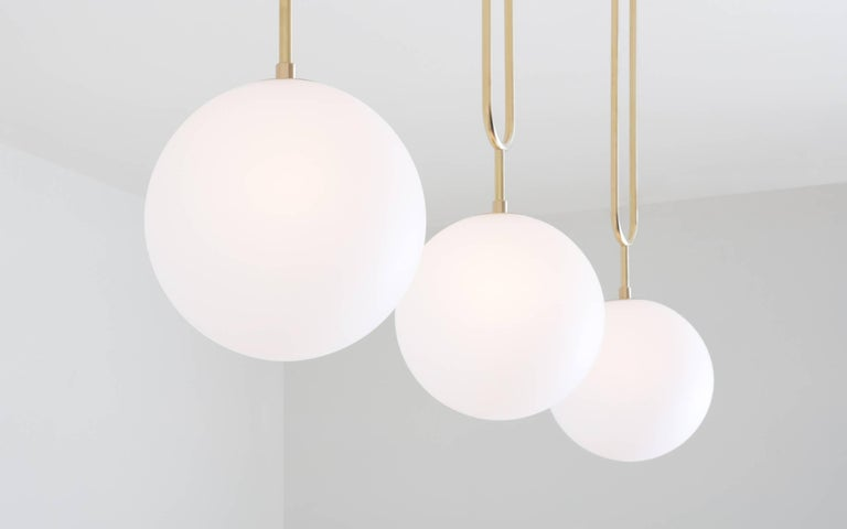 Contemporary Koko, a Modern Pendant Light with Satin Globe Shade in Brushed Brass Finish For Sale