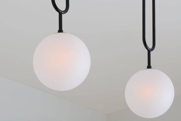 Drawing inspiration from a pearl pendant, the Koko line is elegant and modern, with its luminous blown glass and brass arch detail. A versatile light, Koko can be displayed as a single pendant or arranged in a grouping as a
