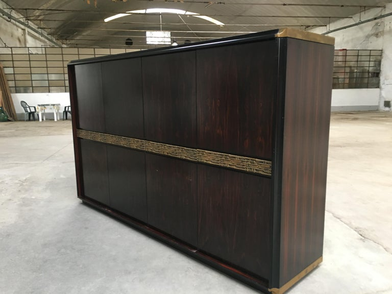 Mid-Century Modern Italian ebony and bronze four shatter wardrobe by Luciano Frigerio for 'Frigerio di Desio' from 1970s. This armoire is equipped with a chest of drawers and a shelf on the left side. Both sides are equipped with sliding hooks for
