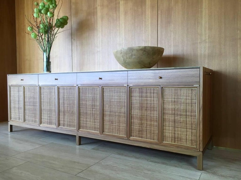 Inspired by the classic midcentury, this solid teak buffet is perfectly suited for a modern interior. A textured solid brass top complements the subtle brass and cane details of the door faces. Blum glides are concealed below the dual solid teak