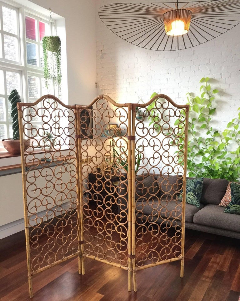 Incredibly stylish French rattan room divider from the 1960's. Palmier-shaped motif gives this piece elegance and sophistication as do the leather straps which bind the canes. Original pieces such as this are becoming more and more rare. In very