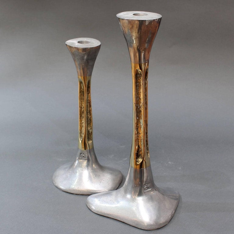 Pair of brutalist aluminium and brass candlesticks by David Marshall, circa 1980s. These brutalist style candlesticks are both weighty and tactile with the maker's mark impressed on the surface near the base. The bottom of the aluminium bases have