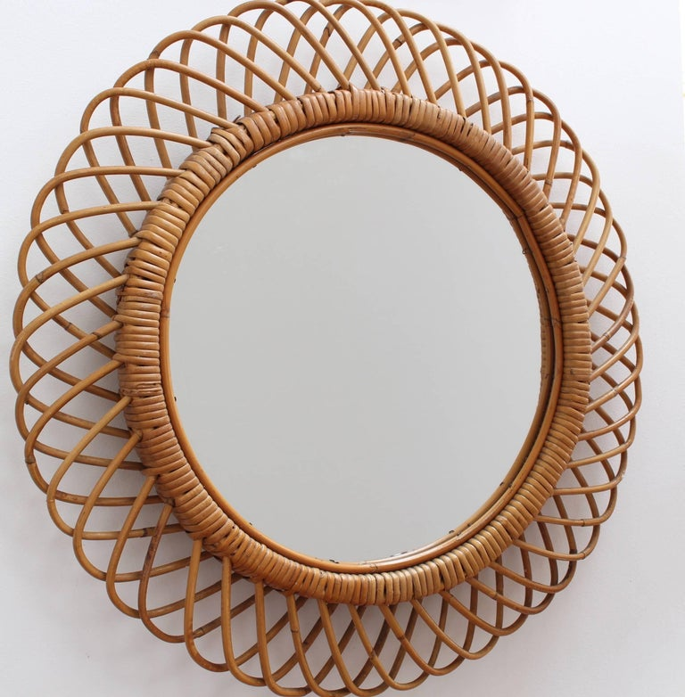 Italian sunburst rattan wall mirror (circa 1960s). This mirror has a very delightful sunburst motif created by a series of rattan horseshoe-shaped 'sunbeams' bound together. There is a characterful, aged patina on the mirror frame. In very good