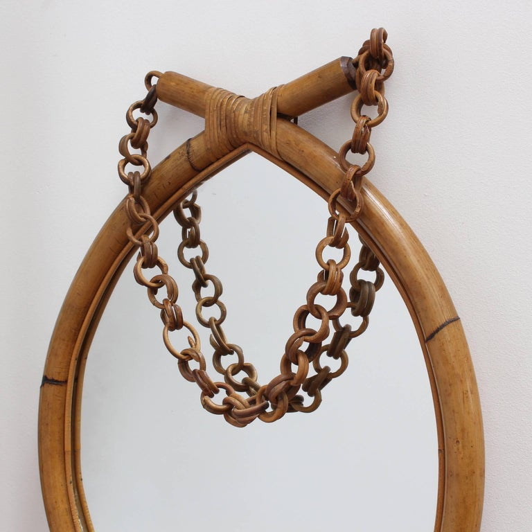 Italian 'eye-shaped' bamboo and rattan wall mirror (circa 1960s). Wide-caned bamboo in the shape of an eye is bound with rattan strips and sports a rattan hanging chain. There is a graceful, aged patina on the mirror frame. In very good vintage