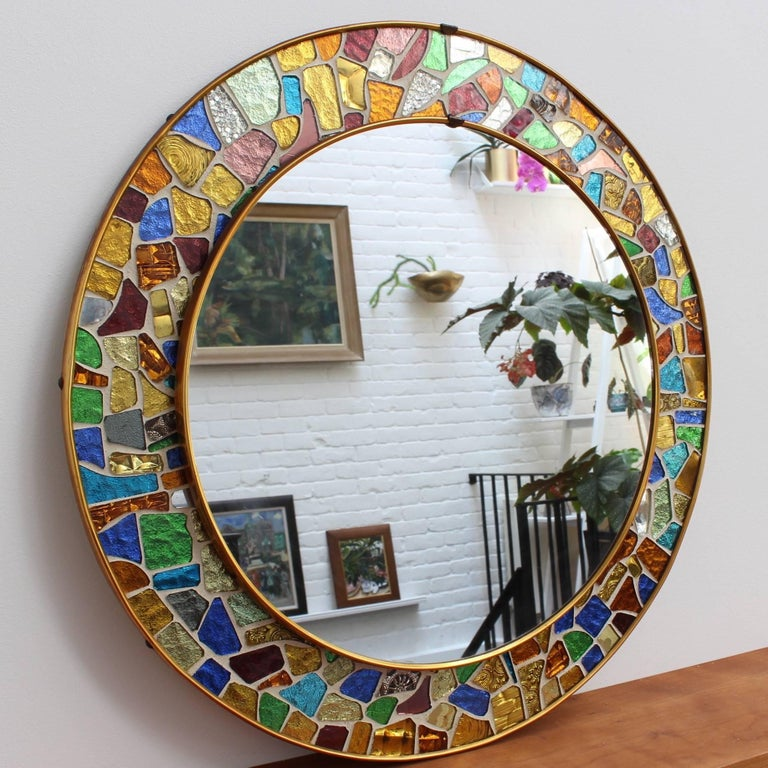 Splendid midcentury circular brass mirror with colorful mosaic surround. Made in the style of Antoni Gaudí's 'Trencadís' technique involving irregularly-shaped hand-cut-glass tiles in different colors. Spanish origin, circa 1960s. A short video clip