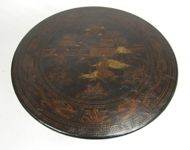 20th century round side table with chinoiserie design and lion's paw feet.