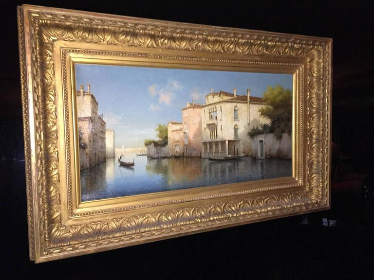 This original oil on canvas painting depicts a quiet summer morning, and a single Gondolier moves elegantly through a Venetian waterway, on his way to pick up a precious cargo of lovers. A blissful blue sky scattered delicately with clouds envelopes