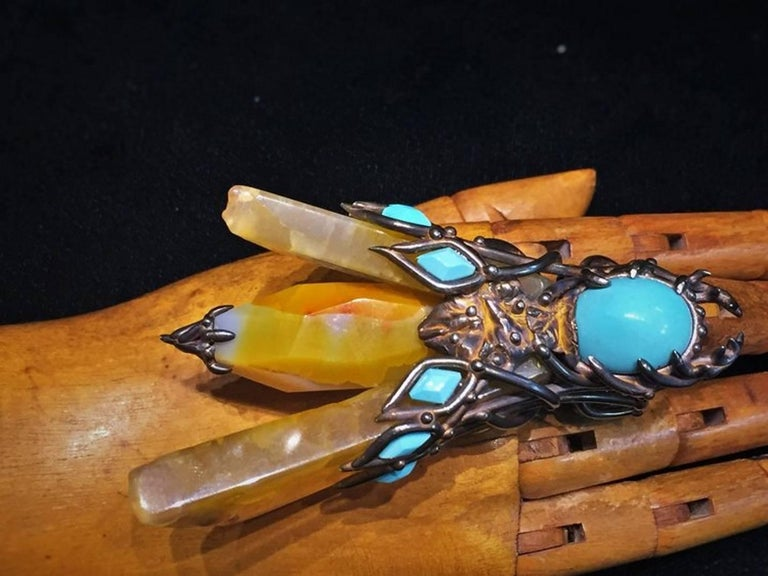 Materials: Sterling silver, orange-yellow agate, Persian turquoise  Dimensions: Max. height 3 3/4 inches  Max. width 2 inches  Ring size 9 (resizable)  Weight: 3.15oz (89.4g)  Val Stern It is a well-known fact that the success of any