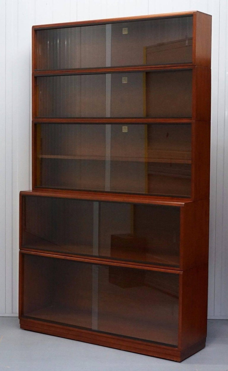 We are delighted to offer for auction this stunning five-piece stacking 1960s section bookcase fully stamped and labeled by Simplex in medium Mahogany and finished with glass sliding doors