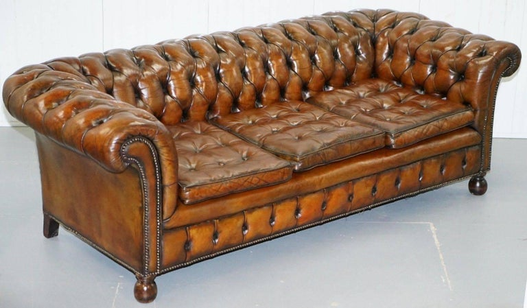 We are delighted to offer for sale this very rare absolutely stunning, circa 1930s fully restored Chesterfield aged whiskey brown leather gentleman's club sofa with Thomas Chippendale style floating buttoned feather filled seat cushions