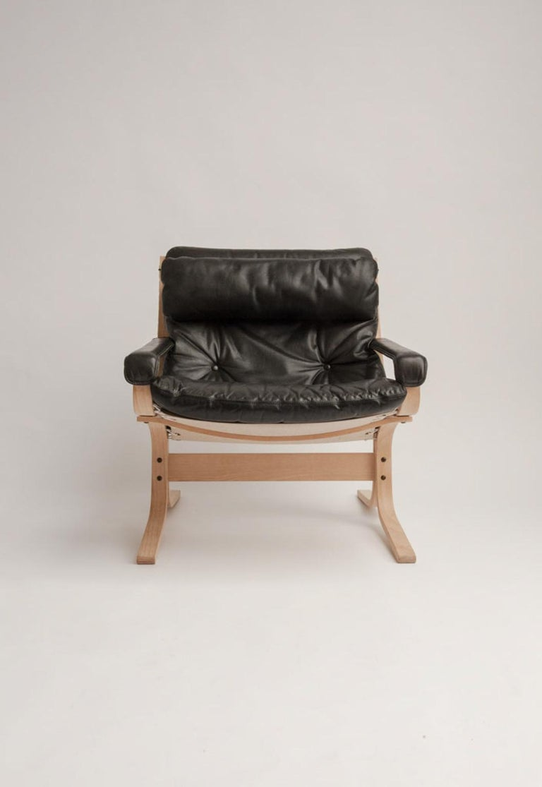 Recliner chair with headrest and ottoman, model Siesta, frame of laminated beech, upholstered in dark gray leather. Produced by Westnofa.