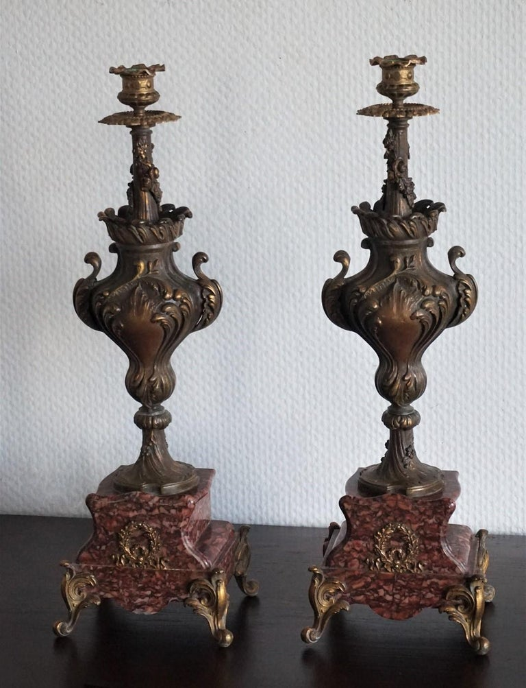 Pair of tall classical urn form candleholders of cast patinated and parcel gilded bronze richly ornate with foliage and floral motifs, on red griotte marble base with gilt bronze feet, circa 1880-1889.
