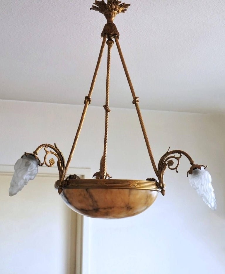 Large early 20th century French  Art Deco gilt bronze six-light chandelier with marble bowl shade suspended from three gilt bronze arms with knotted rope shape. Thee curved arms richly ornate and with flame frosted glass lamp shades. Number of