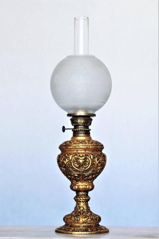 19th century gilded solid high relief cast bronze oil lamp converted to electric table lamp, with etched glass globe and glass chimney, France, circa 1880.  This oil lamp has been converted to electric in the 1950s. One lamp socket  Measures: Total
