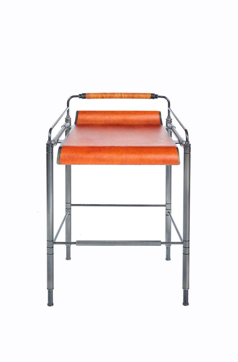 Amuneal's blackened steel and leather stools are fabricated from precision machined and laser-cut steel components. The laser-cut and formed seat is hand clad in leather and suspended from machined connections. The seat back is hand-wrapped in