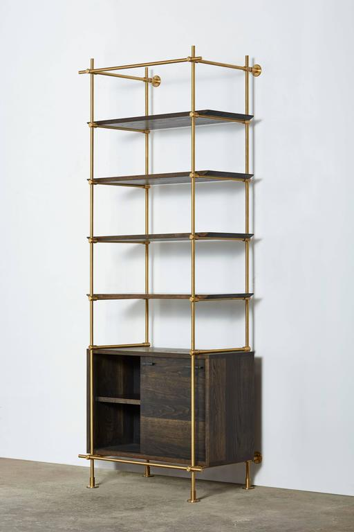 This single bay version of Amuneal's collector's shelving unit features solid machined brass fittings and posts in a warm brass finish. The unit mounts to the floor and to the wall to support a series of easily adjustable shelves and credenza