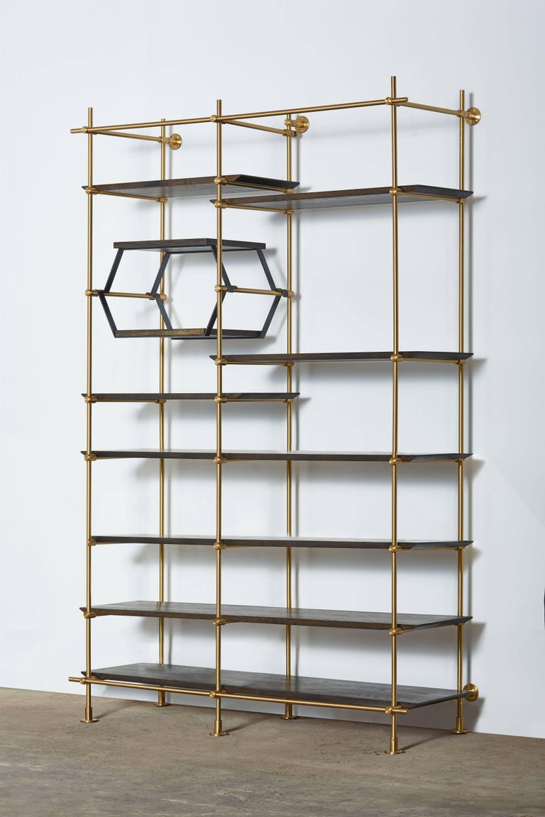 This two-bay version of Amuneal's collector's shelving unit features solid machined brass fittings and posts in a warm brass finish. The unit mounts to the floor and to the wall to support a series of easily adjustable shelves. The wood shelves are