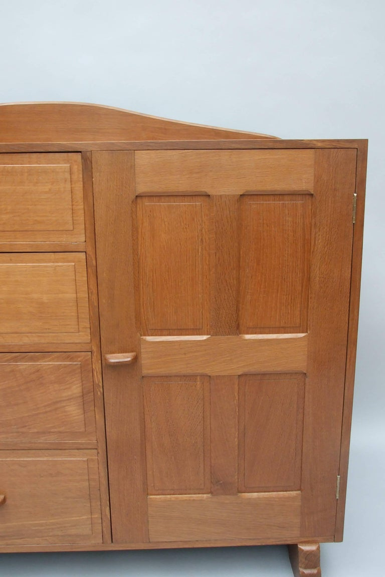 An oak cotswold sideboard with raised fielded panelled doors either side of four graduated fielded panelled drawers, with exposed dovetail and wedge tenon construction to the top and sides, chamfered shaped up-Stand, on sledge feet, and nip handles,